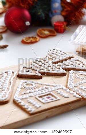 Woman decorating gingerbread cookies in the shape of Christmas tree. Close up view with selective focus.