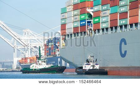 Oakland CA - September 28 2016: Tugboats AMERICA and REVOLUTION at the stern of Cargo ship COSCO FORTUNE assisting the vessel to maneuver out of the Port of Oakland.