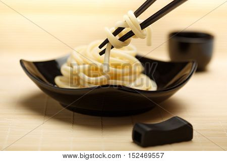 Spaghetti macaroni taking from black ceramic dish by chopsticks at light bamboo mat background with sake cup and chopsticks rest near. Shallow dof. Focus on chopsticks.