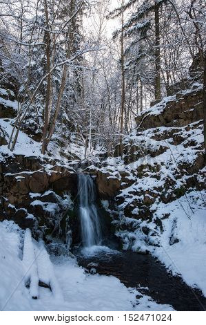 Icy waterfall in the frosty forest with snow