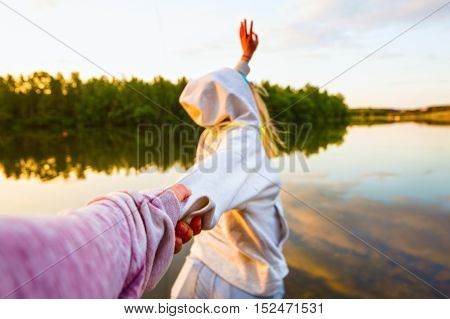 Girl in a white hoodie holding a guy's hand on the beach