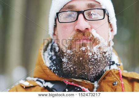 Frozen ice-covered face of a bearded man in a blizzard. Portrait.
