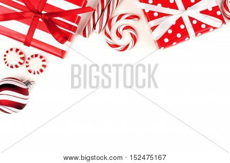 Christmas Corner Border Of Red And White Gifts And Peppermint Candies Over A White Background