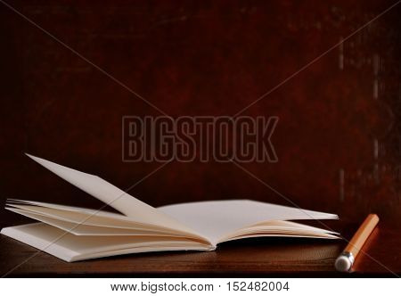 Open diary pocket book and pencil on brown vintage background