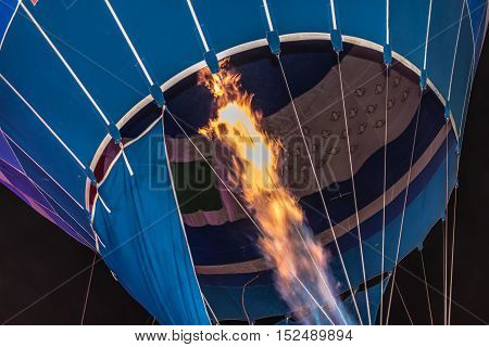 Flames shooting inside a hot air balloon filling it with air getting ready for a launch
