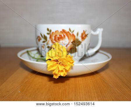 Tea mug and yellow flower on the table