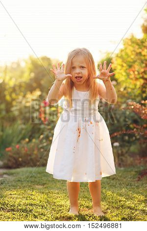 Nice little girl in a white dress dirty scares. Dress in tomato juice. A girl stands barefoot on the lawn.