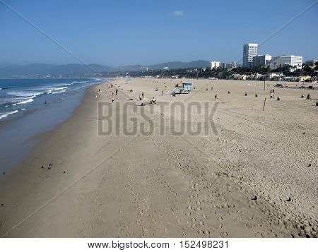 The beach of Santa Monica, with the Atlantic Ocean and, opposite, towers and buildings of the city. Photo taken early morning in May. Daylight / Beach Santa Monica / Santa Monica, California, USA.