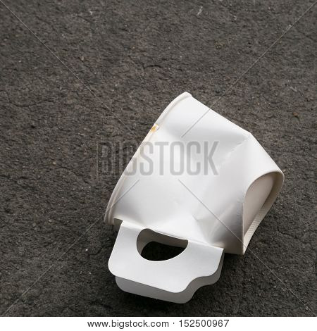 The close up of disposable paper cup garbage (used coffee cup) on cement ground.
