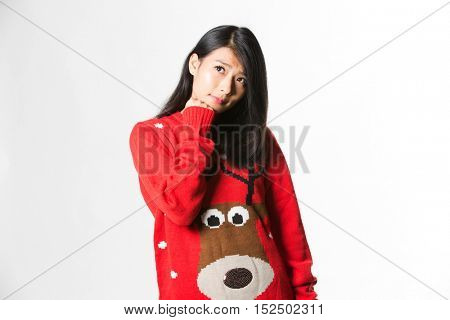 Portrait of woman in Christmas sweater standing thinking about the future