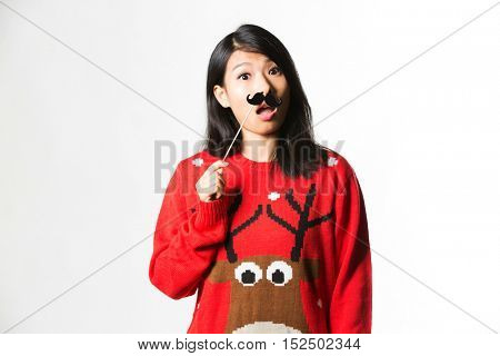 Portrait of woman in Christmas sweater standing with fake moustache
