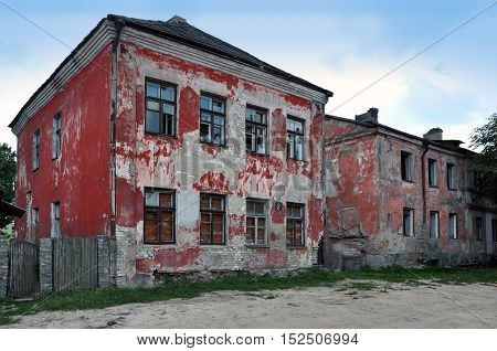 Crumbling red facade with broken windows of two abandoned houses.