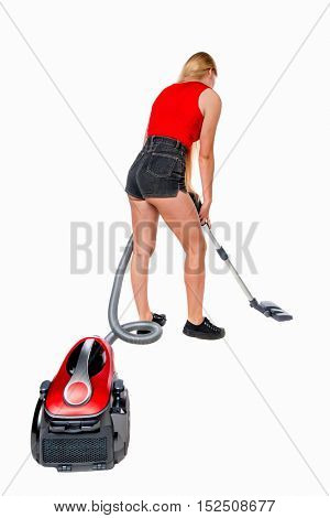 Rear view of a woman with a vacuum cleaner. She is busy cleaning. Rear view people collection.  backside view of person.  I. The girl in shorts with a vacuum cleaner cleans the floor.