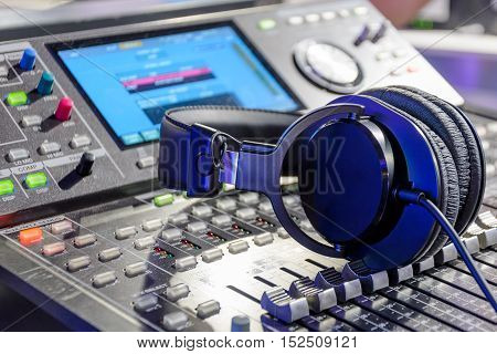 Studio headphones lying on the audio mixer. Live and studio equipment.
