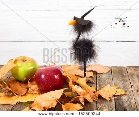 Toy crow in a cap and autumn leaves. On an old table there is a toy in a hat of the witch. The yellow whithered autumn leaves and apples are scattered