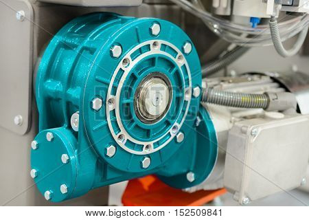 Worm gear motor. Mounted on CNC machine. Abstract industrial background.