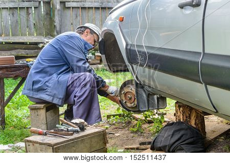 Senior mechanic replaces the vehicle's front wheel. car repair garage in your home.
