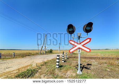 Railway crossing equipped with electric lights. Crossing the road in the countryside.