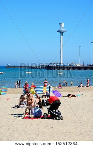 WEYMOUTH, UNITED KINGDOM - JULY 18, 2016 - Holidaymakers on the beach with the Jurassic Skyline tower to the rear Weymouth Dorset England UK Western Europe, July 18, 2016.