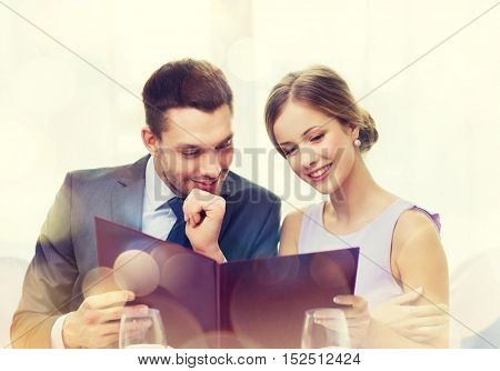 restaurant, couple and holiday concept - smiling couple with menu at restaurant