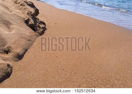 sandy heap on the seashore or the ocean and water inflow closeup
