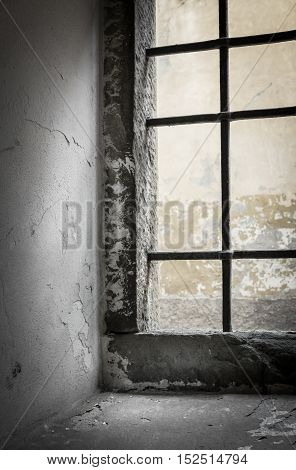 Contrasting light shines through the window of abandoned house. Shallow DOF.