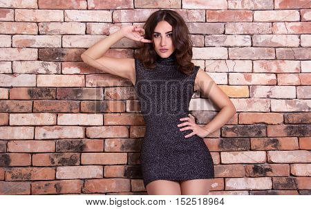 Young beautiful woman in a short dress posing near brick wall. Sexy brunette with a thin waist to trendy slinky dress. Copy space. Sensual beautiful woman near the old wall.