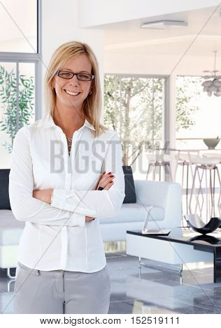 Happy mid adult female caucasian blonde business customer standing at elegant home, arms crossed, smiling, looking at camera, wearing glasses and white casual clothing.