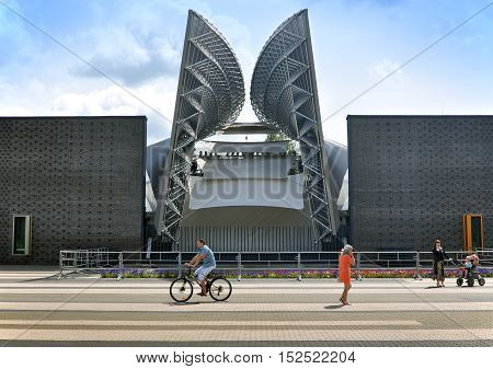 Molodechno, Belarus - July 3, 2014. Facade of modern amphitheater in Molodechno, Belarus. Curve rod metal structure of the facade. Walking people in the foreground.