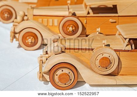 Wooden model of retro executive cars on a white background
