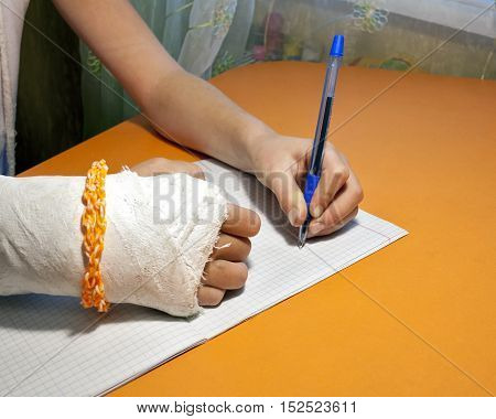 Girl with plastered right hand with the left hand writes a ball pen sheet in a cage
