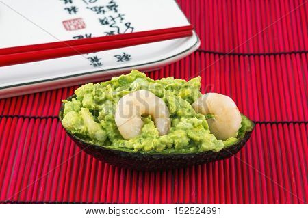 Tasty avocado salad with two shrimps and red chopsticks lies near white plate