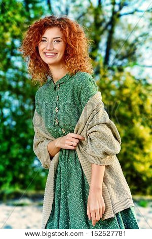 Happy girl with bright curly red hair enjoying sunny autumn day in the park. The mood of autumn, leaf fall. Autumn fashion.