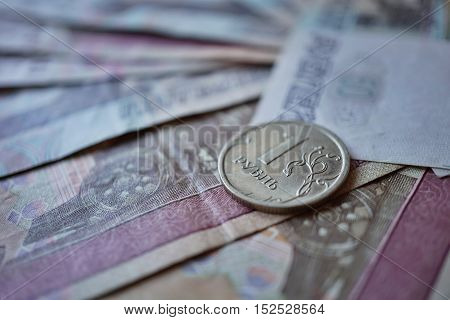 Single coin of one Russian Ruble (currency in Russia - Rubles, RUB) put on the background created of Ruble bank notes