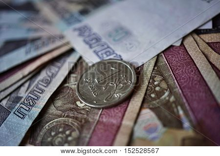 Single coin of one Russian Ruble (currency in Russia - Rubles, RUB) put on the background created of Ruble bank notes poster