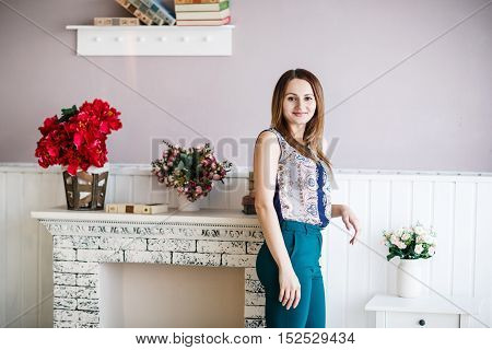 Young woman posing leaned on the sham fireplace in the room