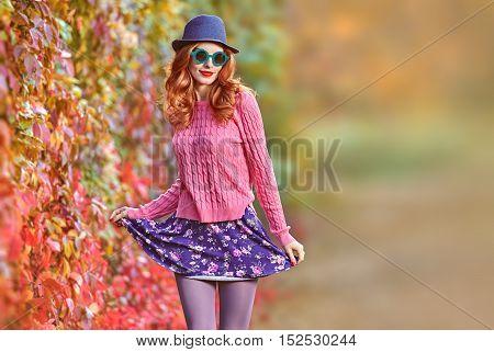 Fall Fashion. Fashion Model woman Stylish Autumn Outfit. Hipster Redhead Crazy Having Fun. Autumn Urban fashion. Outdoor Park. Glamour Sexy Cheeky Girl Fashion Sunglasses Trendy Hairstyle Enjoy Nature