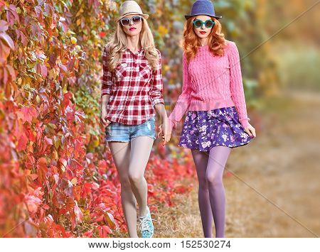 Fall Fashion. Fashion Model woman in Stylish Autumn Outfit. Hipster Friends Sisters Crazy. Autumn Urban fashion. Outdoor Park. Glamour Sexy Cheeky Girl Fashion Sunglasses Trendy Hairstyle Enjoy Nature