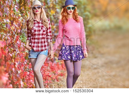 Fashion Model woman in Stylish Autumn Outfit. Fall Fashion. Hipster Friends Sisters Crazy. Glamour Sexy Cheeky Girl Fashion Sunglasses Trendy Hairstyle Enjoy Nature. Autumn Urban fashion. Outdoor Park