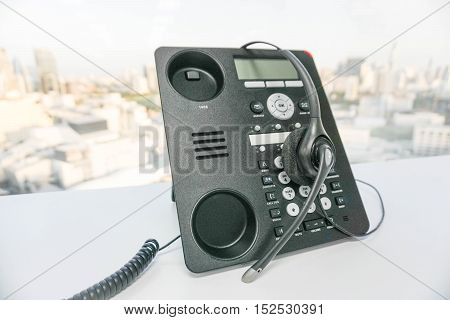 close up IP phone with headset in office