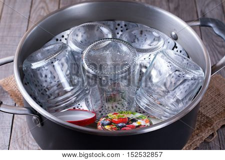 Glass jars for sterilization on a wooden background