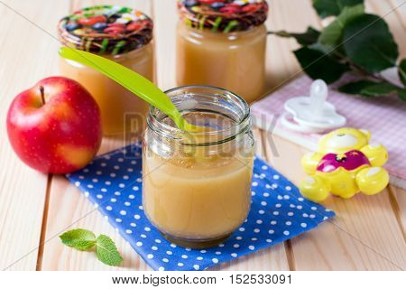 Jar with apple of baby food on a wooden background