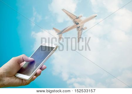 Hand holding smartphone on blurred flying airplane in clear sky background