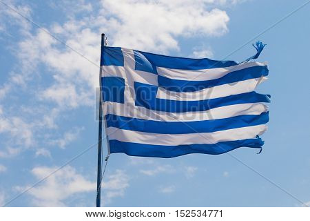 Greek flag flutter on wind against blue sky with white clouds