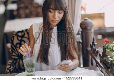 beautiful girl using telephone and drinking mojitos