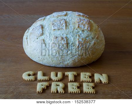 A gluten free loaf of bread with the phrase Gluten Free spelled out using alphabet shaped cookies on a wooden background.