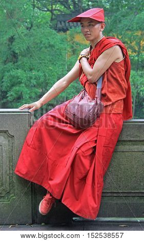 Buddhist Monk In Traditional Clothes Is Resting Outdoor