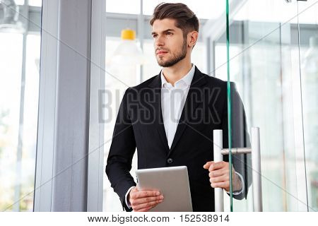 Serious young businesman holding tablet and entering the door in office