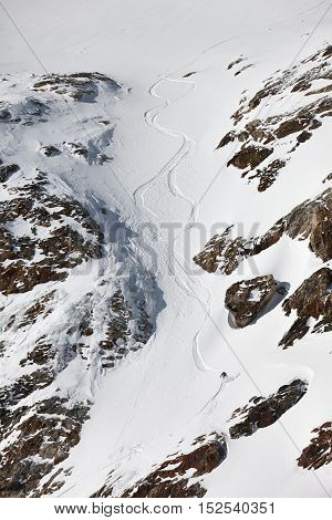Snowboard freeriding between the rocks in Alps. Extreme winter sports.