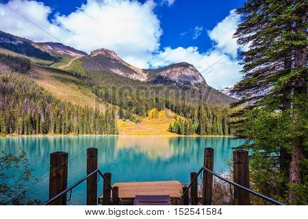 Magic Emerald Lake in Yoho National Park, Rocky Mountains. The descent to the water on the lake promenade. The concept of eco-tourism
